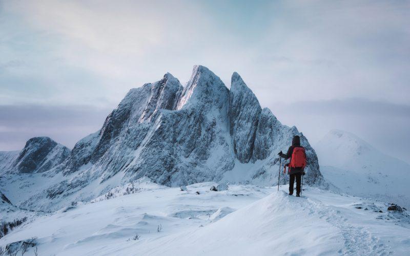 Mountaineer woman standing on top of Segla peak with majestic mountain in snowy on winter at Senja Island